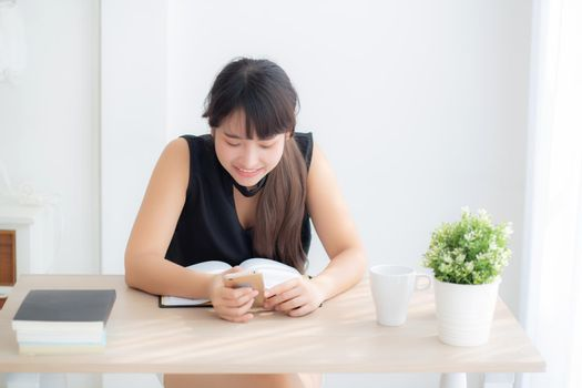 Beautiful young asian woman using touch smart mobile phone chatting message and notebook on desk, asia girl looking social network or check email at table, communication and lifestyle concept.