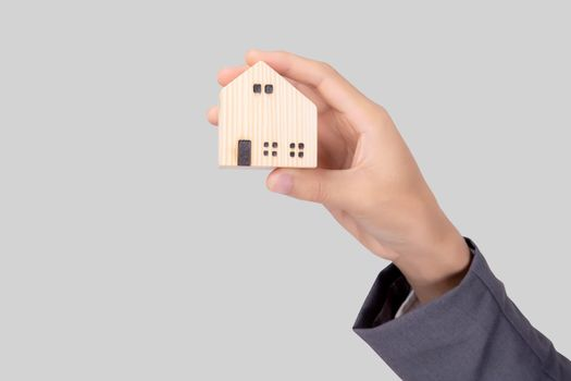 Hand holding the home symbol of saving for future, insurance agent and credit, ownership house, debt and loan of finance, purchase home and refinance, investment about real property, business concept.