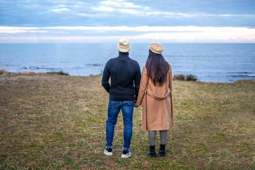 Romance scene of young heterosexual couple view from back holding hands watching the horizon on the sea - Two unrecognizable people wearing fall-winter clothes looking the ocean sunset with cloudy sky