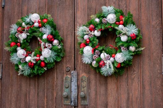 A Large Brown Wooden Door on a Church With Christmas Wreaths On Them