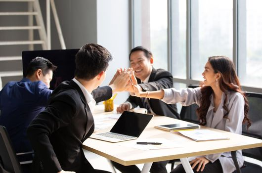 young business team working together at office. Manager pointing at a chart and explaining the analysis about business strategies. Top view shot of business hand shake