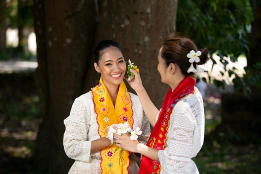 Portrait of a Two young Myanmar woman in a traditional welcoming dress and gesture with flower .