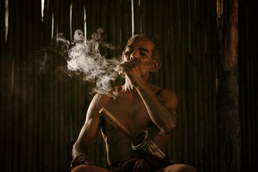 dark and sullen shot of a old man smoking over a black background