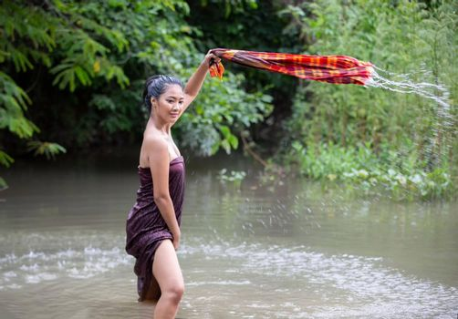 Beautiful Asian women are bathing in the river. Asia girl in Thailand. Asian girl take a shower outdoor from a traditional bamboo chute,countryside Thailand.