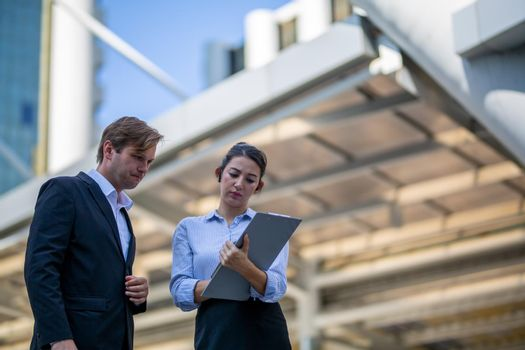 Businessman and women sitting on step outdoor looking on laptop against building