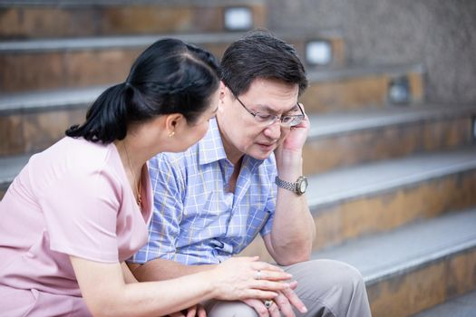 couple elderly sitting on staircase at outdoor.