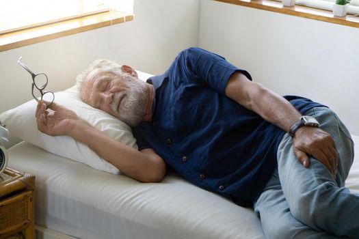 Elderly man sleeping in bed .