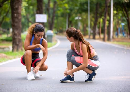 Happy young curvy women jogging together in park. Healthy girls friends running on the city street to lose weight.