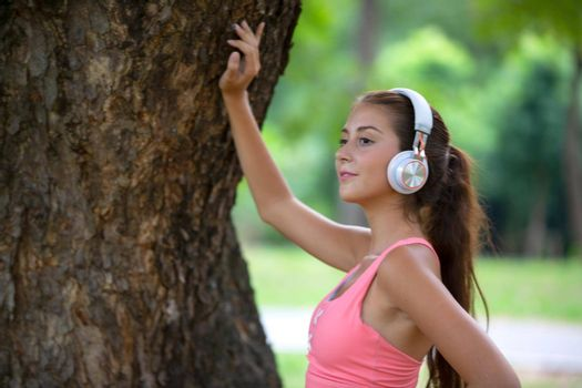 young active women with head phone exercise in park.
