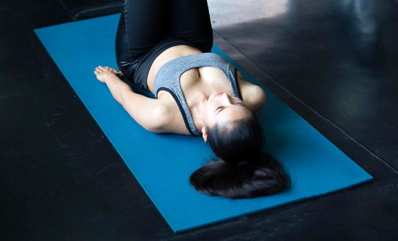 Young attractive smiling woman practicing yoga pose, working out, wearing sportswear pants, bra, full length.