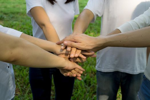 people give hands stack or holding each other for Unity and teamwork concept.