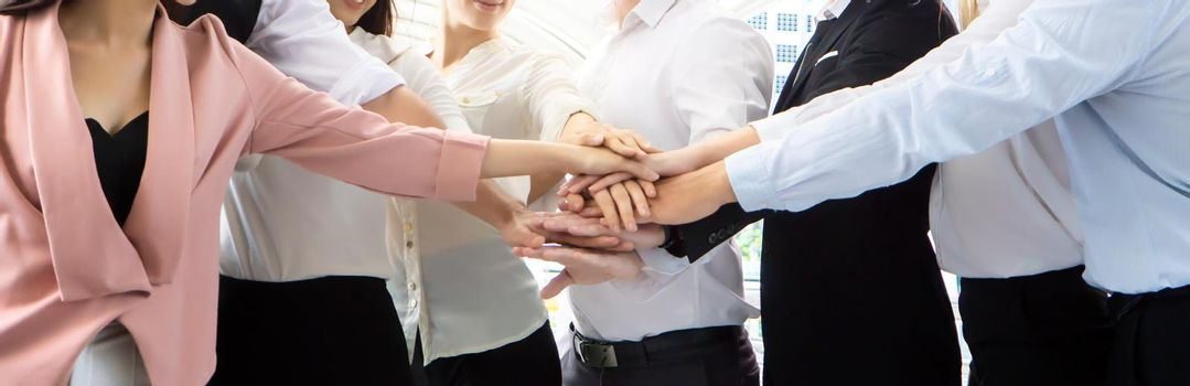 Stack of hands. Unity and teamwork concept. Close up top view of young business people putting their hands together