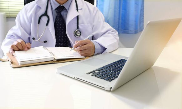 Midsection of Doctor With Arms Crossed Holding Stethoscope with copy space. Healthcare and medical concept.