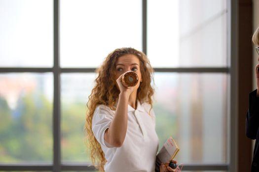 women white shirt with blonde hair drinking water in bottle