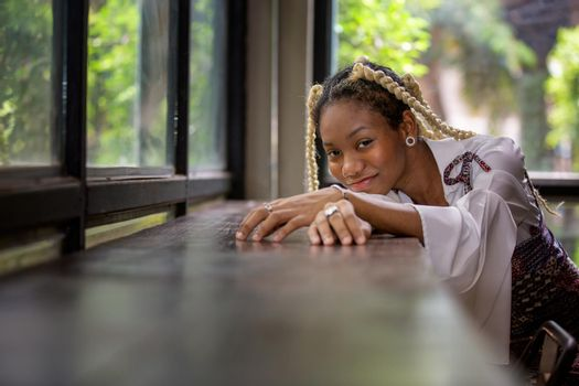 portrait of young african woman showing long braided hair next to face at urban street.