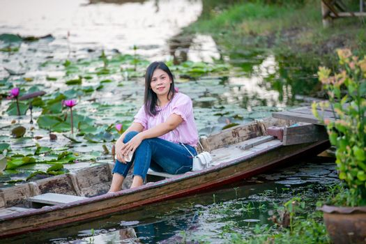 Portrait Of Smiling Young Woman sitting on boat at Outdoors