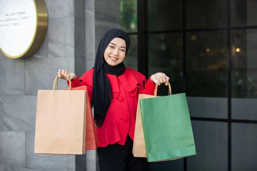 Cheerful young women holding shopping bag at outdoor.