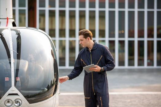 Commercial man pilot in technician suit standing in front of helicopter after check and maintenance engine