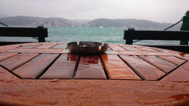 It depicts an ashtray with blurred sea view during rainfall