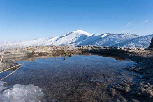 It depicts a small lake and a big snowy mountain in Winter