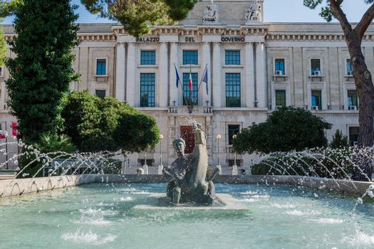 """Front view of the fountain """"La Pescara"""", by G. Di Prinzio, bronze sculpture of a woman riding a horse. Government offices for the Province of Pescara (Abruzzo, Italy) in background."""