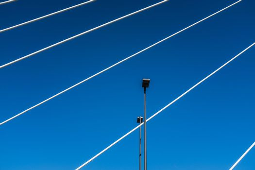 Pescara, Italy: white steel cables of a suspension bridge intersect with street lights. Abstract composition against a bright blue sky.