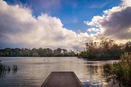 A view of a jetty on the side of a lake, surrounded by trees, during autumn, with green, yellow and orange leaves, and a cloudy sky.