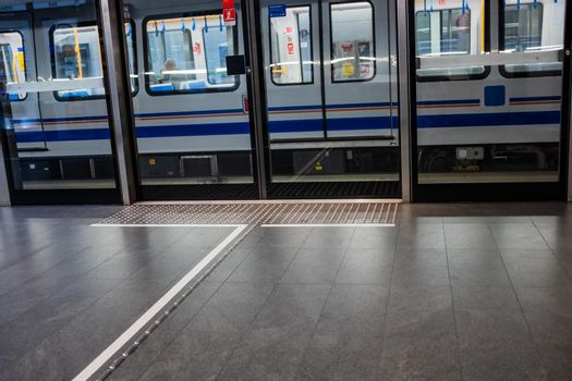 Brescia, Lombardy/Italy: a train leaving from Europa Station on the Brescia Metro. The platform is equipped with screen doors and tactile ground surface indicators as a guide to help visually impaired or blind pedestrians reach the positions of the train access doors.