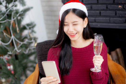 Young asian woman selfie video call online with friends and show glass in Christmas day on phone at home with social distancing, new normal, female video conference, communication and holiday concept.