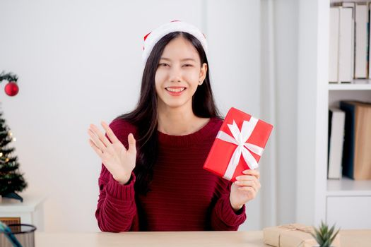 Young asian woman selfie video call online with friends and show red gift box in Christmas day look at camera at home, social distancing, new normal, female video conference, communication and holiday.