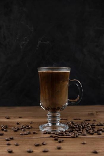 Steaming coffee over wooden surface and black background