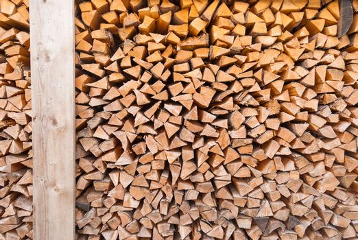 Chopped wood piled in a woodpile and prepared for heating in winter. Alpine Switzerland