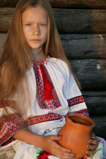 Slavic girl in an embroidered shirt with a clay jug. Ukrainian girl. The blonde in national dress.