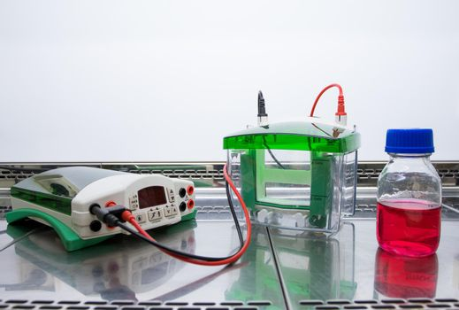 Equipment and a flask with a red liquid are placed in a glass sterile cabinet. Preparing for the experiment with the red liquid. Equipment for electrophoresis.
