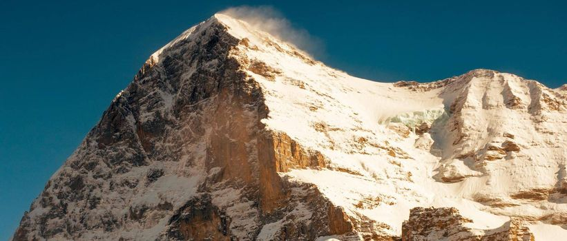 The North wall of Eiger peak in winter with a clear blue sky and a snow flag over the top. Grindelwald Switzerland