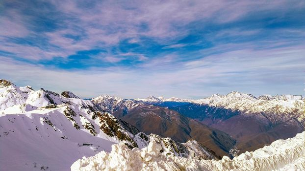 Winter mountain landscape with a view of the Caucasus range covered with snow on a Sunny day. Krasnaya Polyana, Sochi Russia