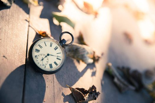 Vintage pocket watch on a wood board, colourful leaves, autumn, sunshine