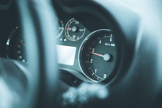 Dashboard of a sports car, steering wheel blurry