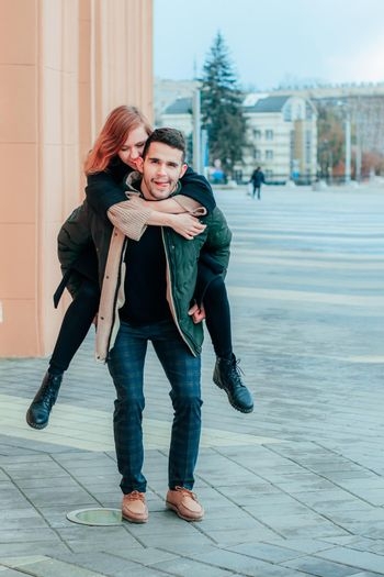 Cheerful Young Couple Hanging on the Street. Two Happy Loving People Having Fun Outdoors - Long Shot Portrait