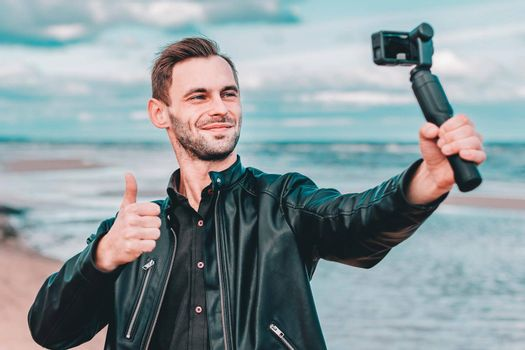Youthful Blogger Making Selfie or Streaming Video at the Beach Using Action Camera with Gimbal Camera Stabilizer. Handsome Guy in Black Clothes Making Photo Against the Sea