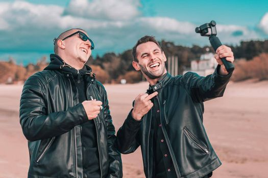 Two Handsome Smiling Friends Making Selfie Using Action Camera with Gimbal Stabilizer at the Beach. Youthful Men in Black Clothes Having Fun by Making Photos