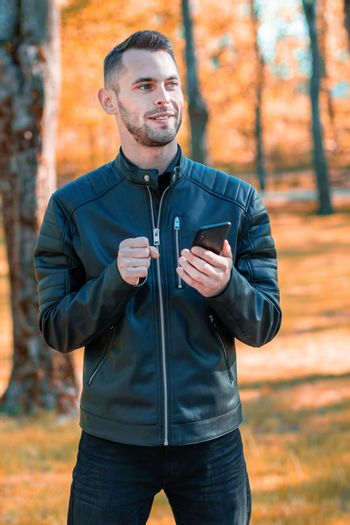 Youthful Satisfied Guy Using Black Smartphone at the Beautiful Autumn Park. Handsome Smiling Young Man with Mobile Phone at Sunny Day - Medium Long Shot