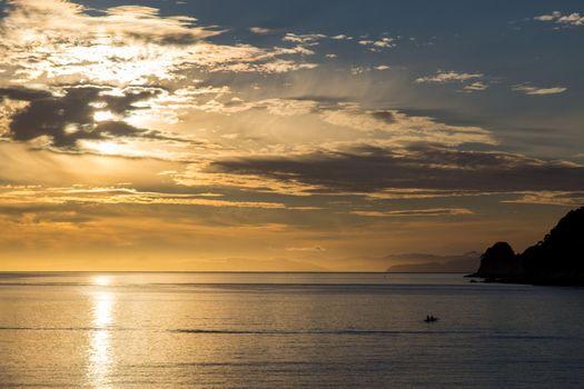 Silhouette of a kayak at sunrise in Abel Tasman National Park, New Zealand.