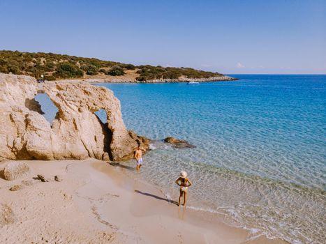 Tropical beach of Voulisma beach, Istron, Crete, Greece ,Most beautiful beaches of Crete island -Istron bay near Agios Nikolaos drone aerial view, couple walking on the ebach