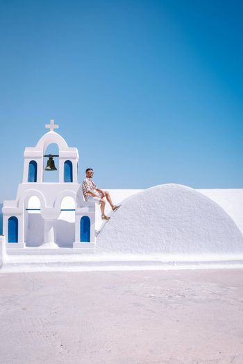 Santorini Greece, young man on luxury vacation at the Island of Santorini watching sunrise by the blue dome church and whitewashed village of Oia Santorini Greece during sunrise during summer vacation, men on holiday in Greece