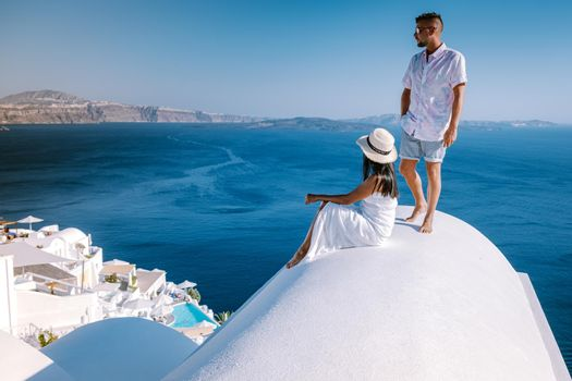 couple men and woman on vacation Santorini, View to the sea and Volcano from Fira the capital of Santorini island in Greece Europe