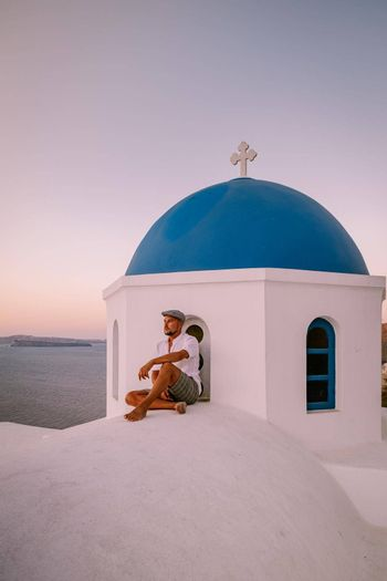 Santorini Greece, guy on vacation in Greece, young men on a luxury holiday at the island of Oia Greece Europe