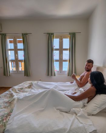 couple in white bed looking out over ocean during luxury vacation in Greece. High quality photo