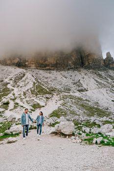 couple mid-age men and woman visiting the Italian Dolomites in Italy. Europe Drei Zinnen Tre Cime di Lavaredo