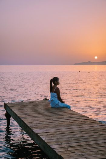 young mid age asian woman on wooden pier at the beach in sunrise time with golden sky. Vacation and travel concept. . Crete Greece